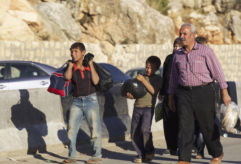 Des civils syriens marchent vers la frontière turque, en octobre 2013.