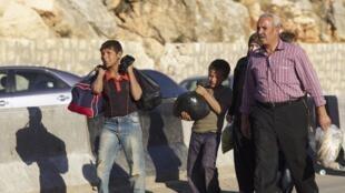 Des civils syriens marchent vers la frontière turque, le 22 octobre.