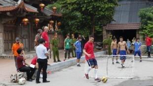 Le joueur d'Arsenal, Laurent Koscielny (C), joue avec des enfants de Hoang Anh Gia Lai, à Hanoï, le 16 juillet 2013.