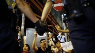 Des militants prodémocratie font face aux forces de l'ordre, devant l'entrée du siège de la police hongkongaise, à Wan Chaï, le 15 octobre 2014.