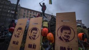 Manifestantes com cartazes com fotos de Yanukovitch pedem a demissão do presidente ucraniano.