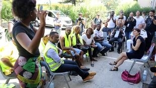 French Overseas Minister Annick Girardin (R) listens to a Yellow Vest (Gilet Jaune) protester gesturing during a meeting at Saint-Paul sous-prefecture, west of the Indian Ocean island of La Reunion, on November 30, 2018.