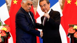 Le conseiller d'Etat et ministre des Affaires étrangères Wang Yi salue son homologue dominicain Miguel Vargas pendant la cérémonie de signature d'un accord entre les deux pays, le 1er mai 2018 à Pékin.