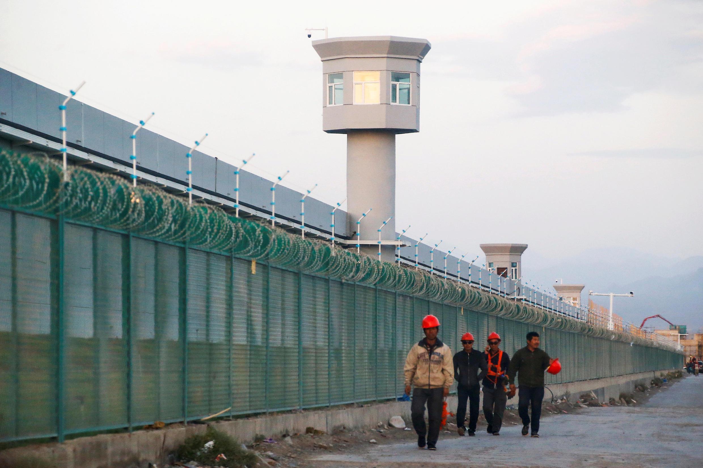Рабочие идут вдоль ограды строящегося «лагеря перевоспитания»  в Синьцзяне 2018 г.