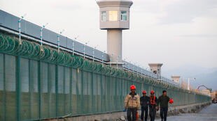 Workers walk by the perimeter fence of what is officially known as a vocational skills education centre, under construction in Dabancheng in Xinjiang Uighur Autonomous Region, China.