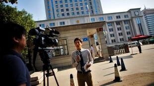 Um repórter em frente ao tribunal onde ocorrerá o julgamento de Bo Xilai