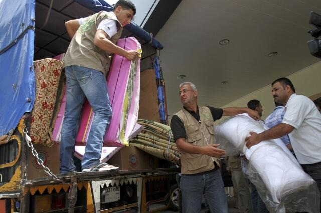 Men carry mattresses from a vehicle as aid to Syrian refugees in Tripoli