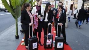 Des militants de l'ONG Oxfam se sont déguisés en banquiers prenant l'avion pour s'exiler dans des paradis fiscaux avec des valises estampillées avec les noms des cinq grandes banques françaises mises en cause, lundi 27 mars 2017.