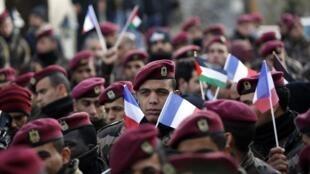 Les membres des forces de sécurité palestiniennes agitent des drapeaux palestiniens et français, lors d'un rassemblement organisé à Ramallah, en janvier 2015.