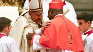 O papa Francisco abraça o novo cardeal centroafricano Dieudonné Nzapalainga durante a cerimónia na  Basílica de São Pedro. 19 de Novembro de 2016