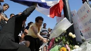 A woman places a bouquet of flower with others to pay tribute to victims near the scene where a truck ran into a crowd at high speed killing scores and injuring more who were celebrating the Bastille Day national holiday, in Nice, France, July 15, 2016