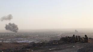 Des peshmergas regardent la fumée s'élever de la ville de Makhmur, dans la région d'Erbil, au nord de l'Irak, après des frappes américaines, le samedi 9 août 2014.