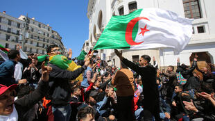 Students chant slogans and carry national flags during a protest after parliament appointed Abdelkader Bensalah as interim president, in Algiers on April 9