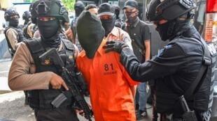 La police indonésienne escorte les suspects à une conférence de presse à Jakarta, le 17 mai 2019.