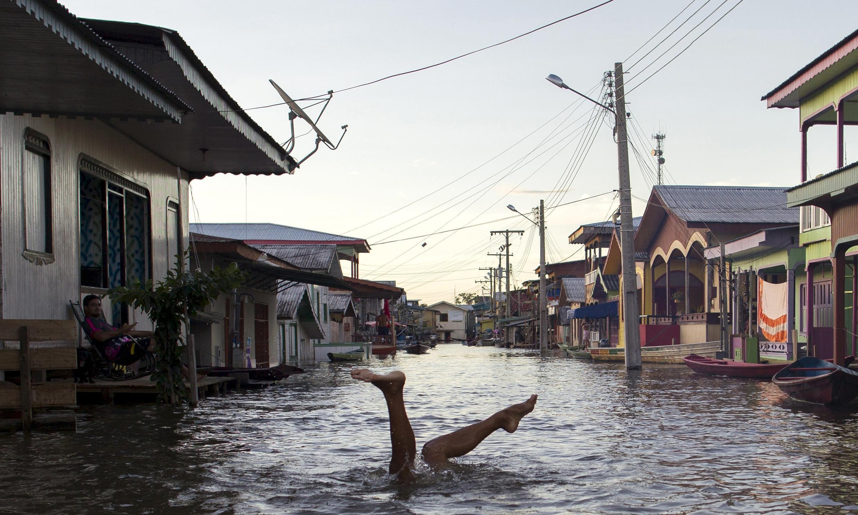 Un enfant joue dans une rue d'un village inondé par une des deux branches du fleuve Amazone, au Brésil.