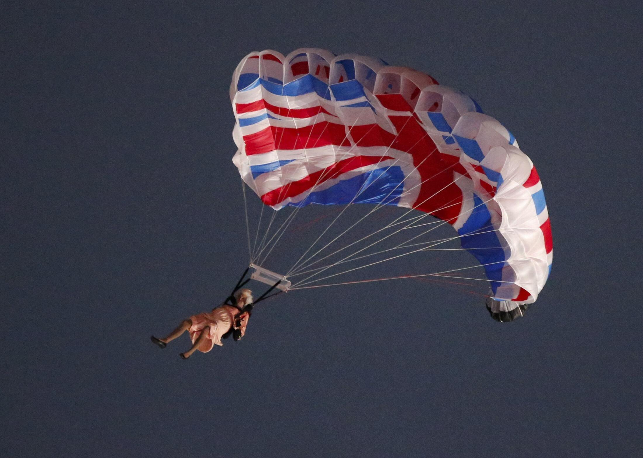 Queen  Elizabeth II - or an actress playing her- parachutes from a helicopter, courtesy Danny Boyle
