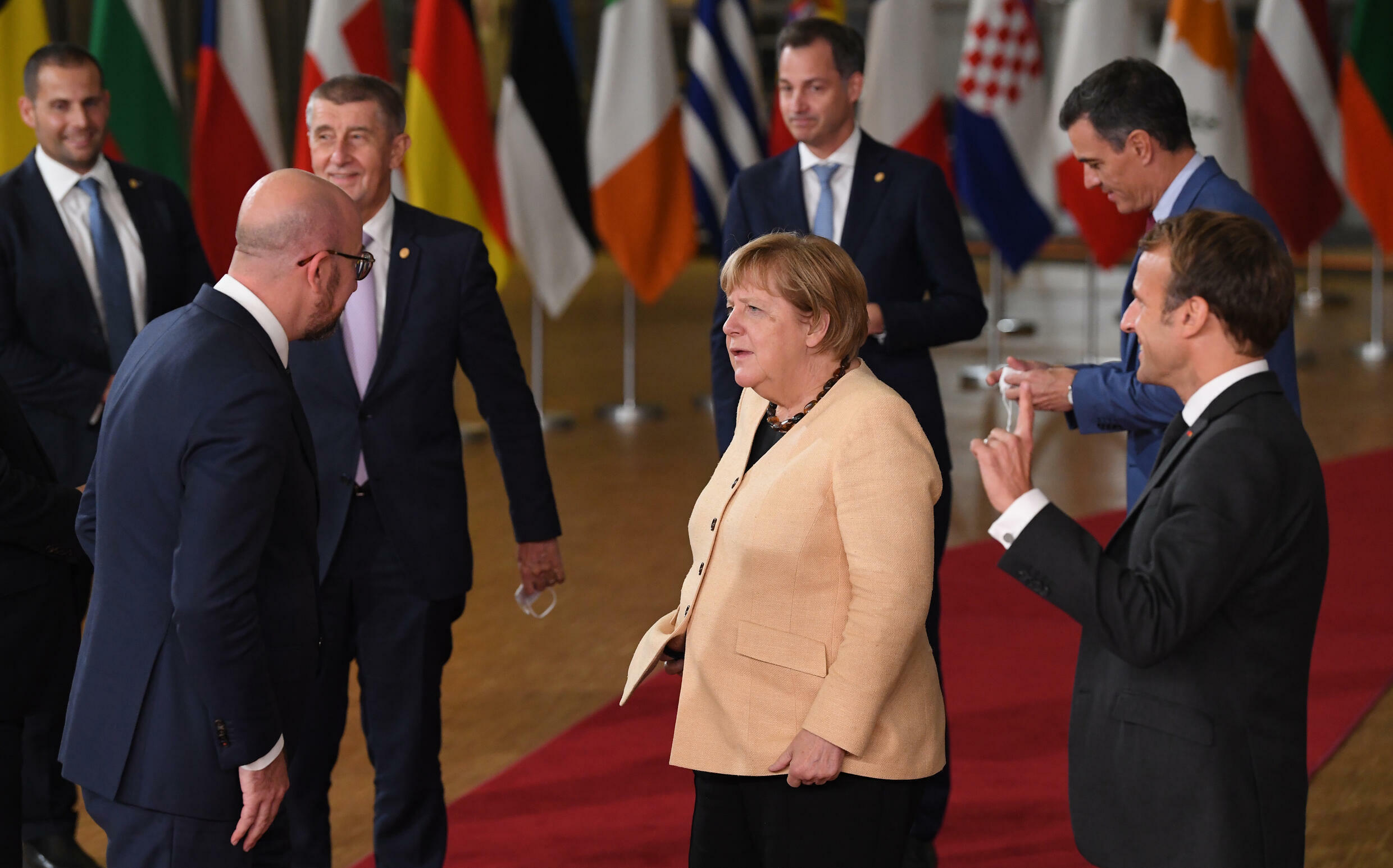 Merkel in her light jacket stood out from the dark suits of her counterparts in a summit group photo