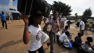 Des familles s'organisent pour fuir le quartier d'Abobo à Abidjan, le 18 mars 2011, au lendemain des bombardements.
