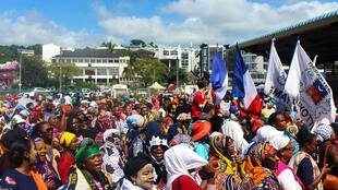 Protesters hold French and Mayotte flags as they gather on the Place de la Republique in Mamoutzou, on the French Indian Ocean island of Mayotte, on 13 March, 2018.