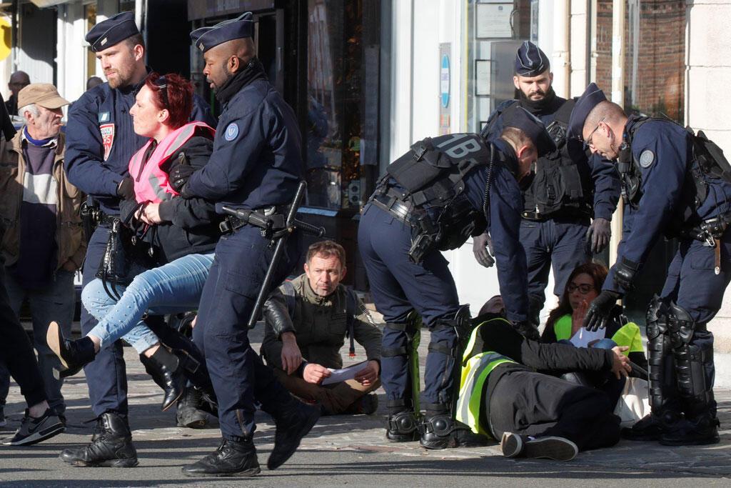Полиция и активисты движения «желтых жилетов» перед приездом президента Макрона в город Альбер на севере Франции 9 ноября 2018.
