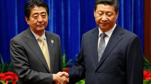 La rencontre entre le Premier ministre japonais Shinzo Abe (G) et le président chinois Xi Jinping, en marge de l'Apec en 2014, a amorcé un timide dégel.
