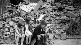 Children sitting outside the wreckage of what was their home, hit by a bomb in September 1940 during the German bombing air raids, known as The Blitz.
