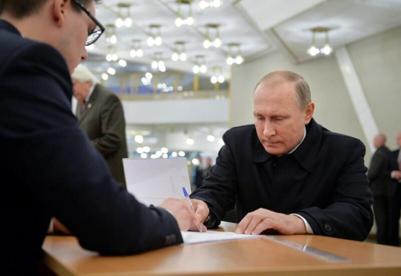 Russian President Vladimir Putin signs a document before getting a ballot at a polling station during a parliamentary election in Moscow, Russia, September 18, 2016.