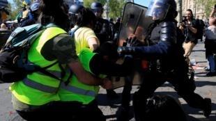 """Policial contém avanço de """"coletes amarelos"""" na Praça da República, neste sábado (20), em Paris."""