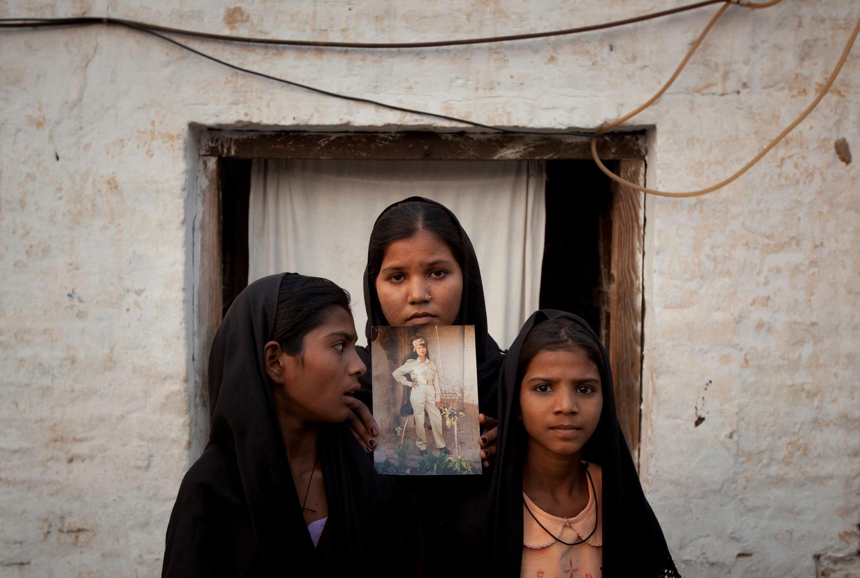 阿薩亞.比比的三個女兒在自家門口舉着媽媽的照片聲援