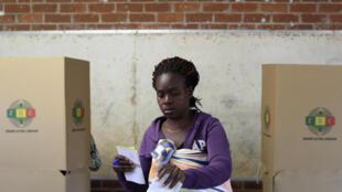 Uma jovem coloca o seu buletim de voto na urna, em Harare - 30 de Julho de 2018