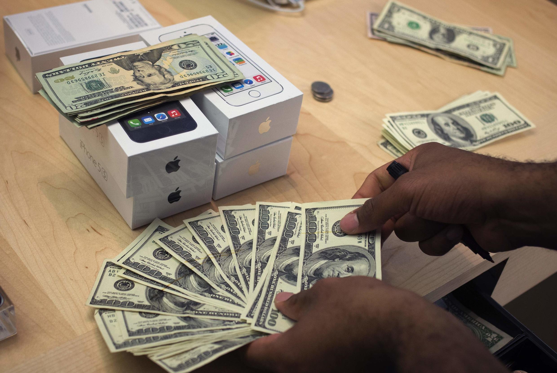 Vendedor conta dinheiro arrecadado com a venda do novo IPhone 5S em loja da 5ª Avenida em Nova York.