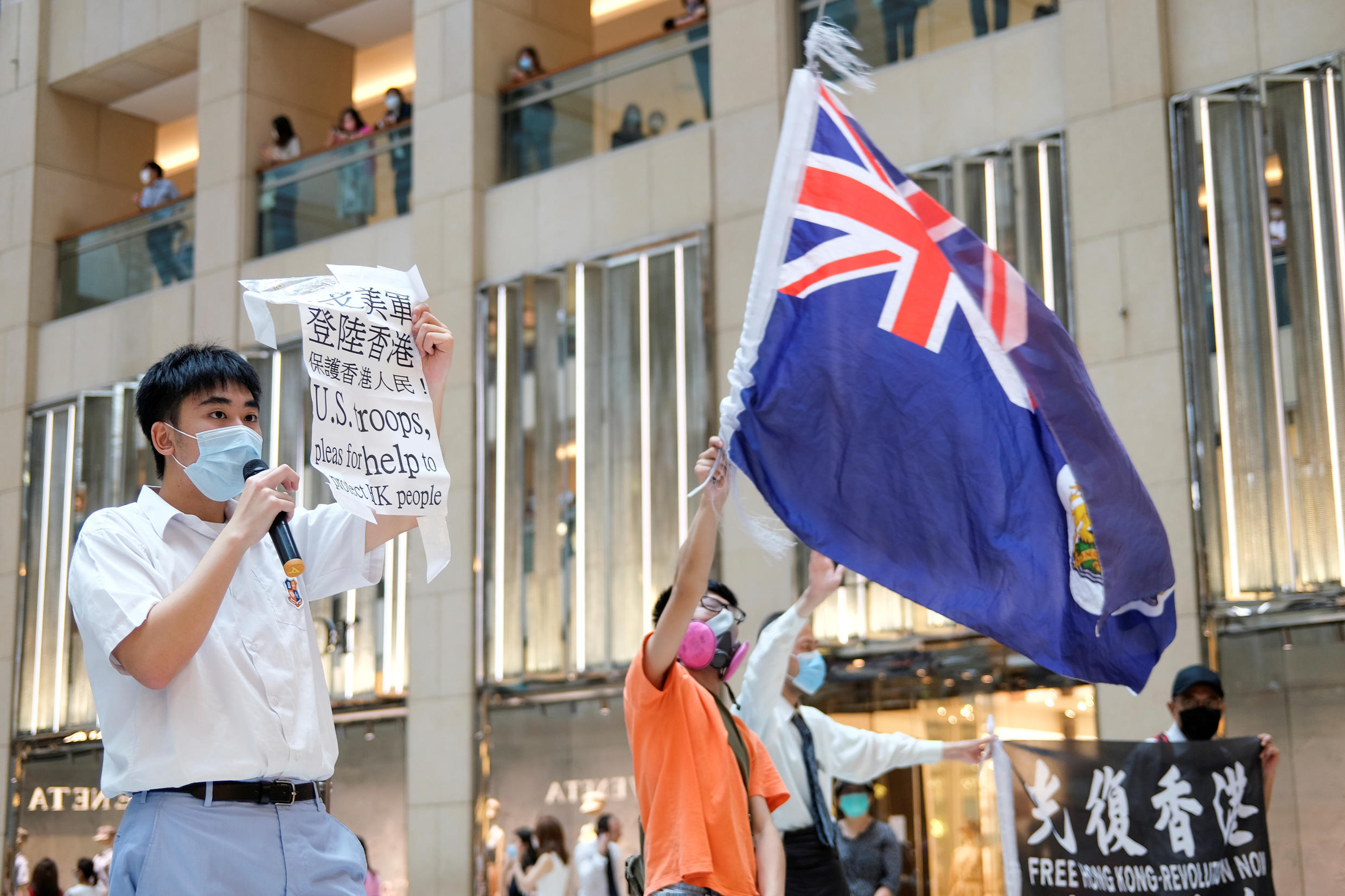 A pro-democracy demonstrator wearing a face mask waves the British colonial Hong Kong flag as another one holds a sign during a protest against new national security legislation in Hong Kong, China June 1, 2020.