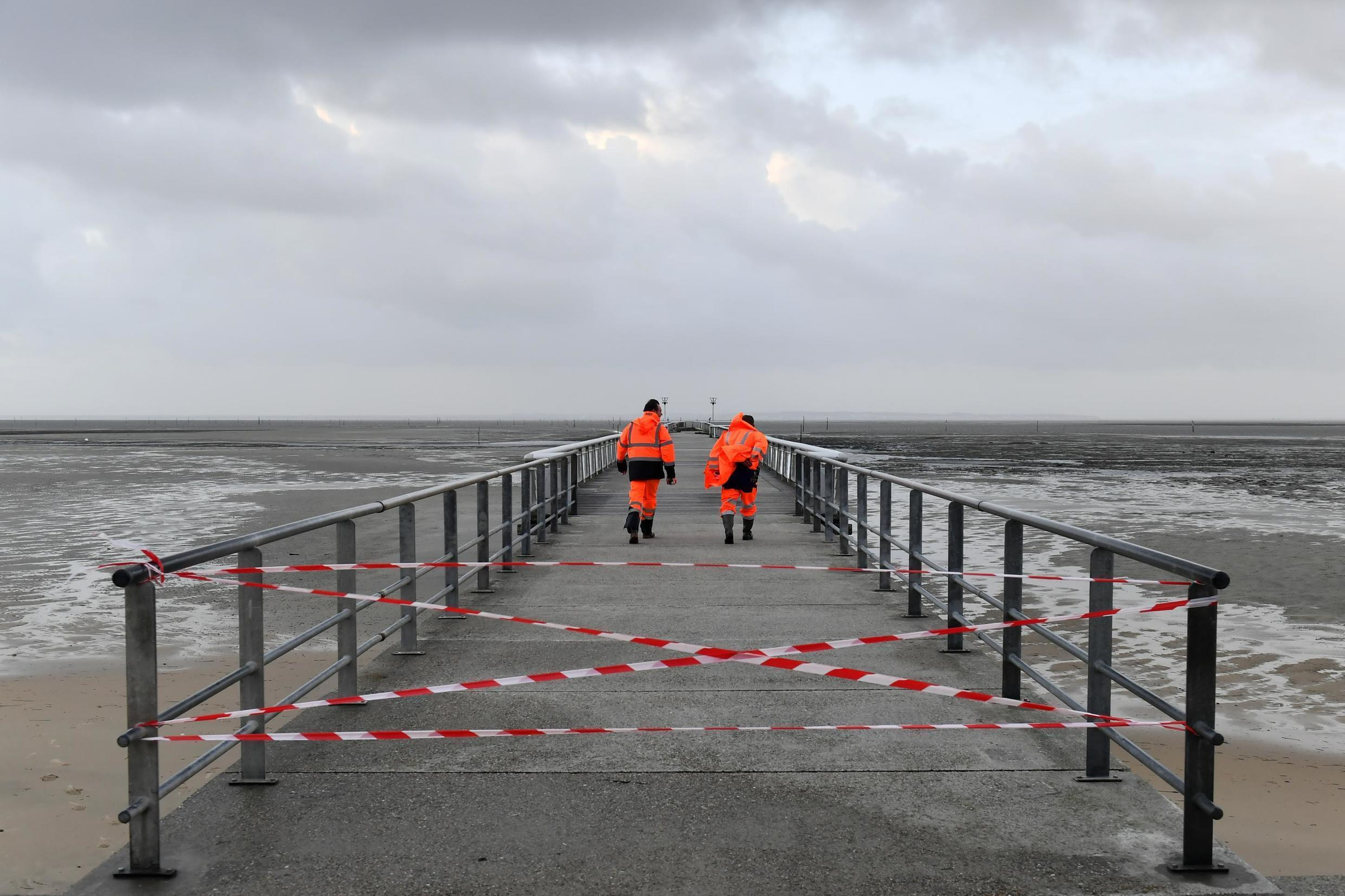 City workers walk on a forbidden pier in the Arcachon basin city of Andernos on December 22, 2019, on the morning after the winter storm 'Fabien'.
