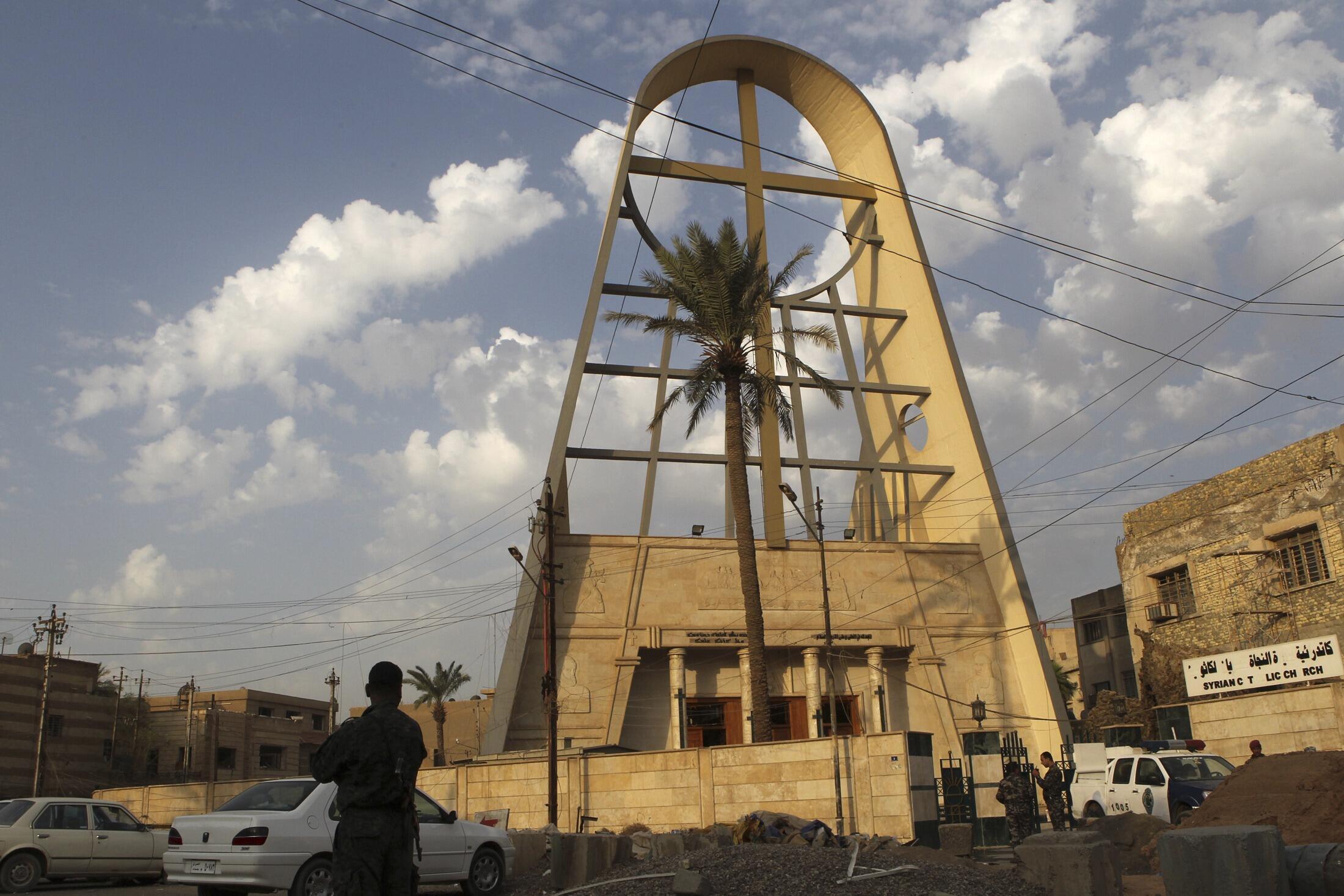 Policiais vigiando a entrada da igreja Nossa Senhora da Salvação em Bagdá, Iraque.