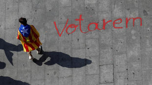 """Un joven con una estelada (bandera separatista catalana) camina sobre un graffiti que dice """"Votaremos"""" durante una marcha en favor del referéndum prohibido del próximo 1 de octubre."""