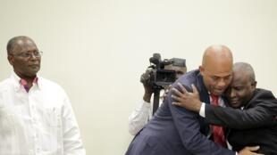 Le président haïtien Michel Martelly (au centre) dans les bras du président de la chambre des représentants Cholcer Chanzy, sous le regard du patron du Sénat Jocelerme Privert, le 6 février 2016 à Port-au-Prince.