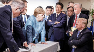 German Chancellor Angela Merkel, flanked by other G7 leaders, talks to Donald Trump in La Malbaie on Saturday