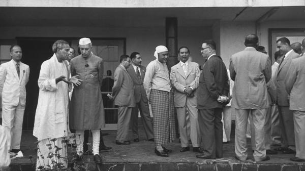 A gauche, V. K. Krishna Menon discute avec Jawaharlal Nehru et à droite, Gamal Abdel Nasser s'entretient avec d'autres représentants lors de la conférence de Bandung.