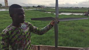 un jeune de Ganvié tient une éolienne fabriquée avec des matériaux recyclés