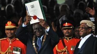 Raisi Mwai Kibaki wa Kenya (katikati) akinyanyua katiba mpya baada ya kutisa saini mwaka jana