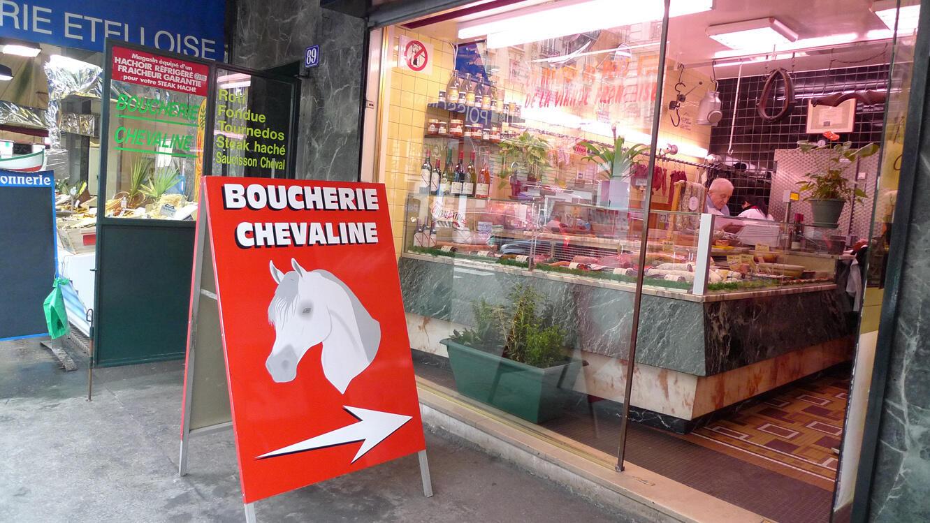 Butcher Jacques Leban mincing horsemeat at his shop in Paris
