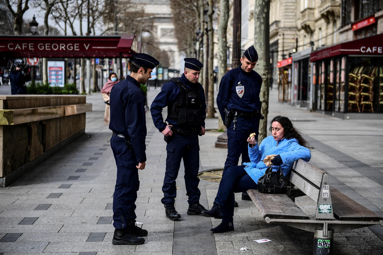 Policías franceses controlan a una mujer sentada en un banco en la avenida de los Campos Elíseos en París, el 17 de marzo de 2020, al inicio de un confinamiento a causa del coronavirus