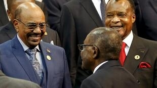 Le président du Soudan, Omar el-Béchir, aux côtés de son homologue congolais Denis Sassou-Nguesso, salué par le chef de l'Etat du Zimbabwe Robert Mugabe, lors du 25e sommet de l'UA en Afrique du Sud, Johannesburg, le 14 juin 2015.