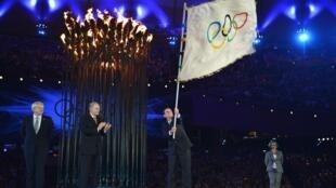 Eduardo Paes, prefeito do Rio de Janeiro (d), recebe a bandeira olímpica do prefeito de Londres, Boris Johnson (e), neste domingo, durante o encerramento dos Jogos.
