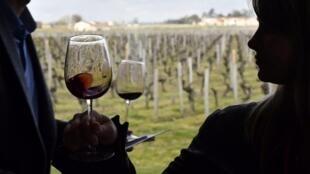 Visitors taste red wine at the Chateau la Dominique in Saint-Emilion, southwestern France.