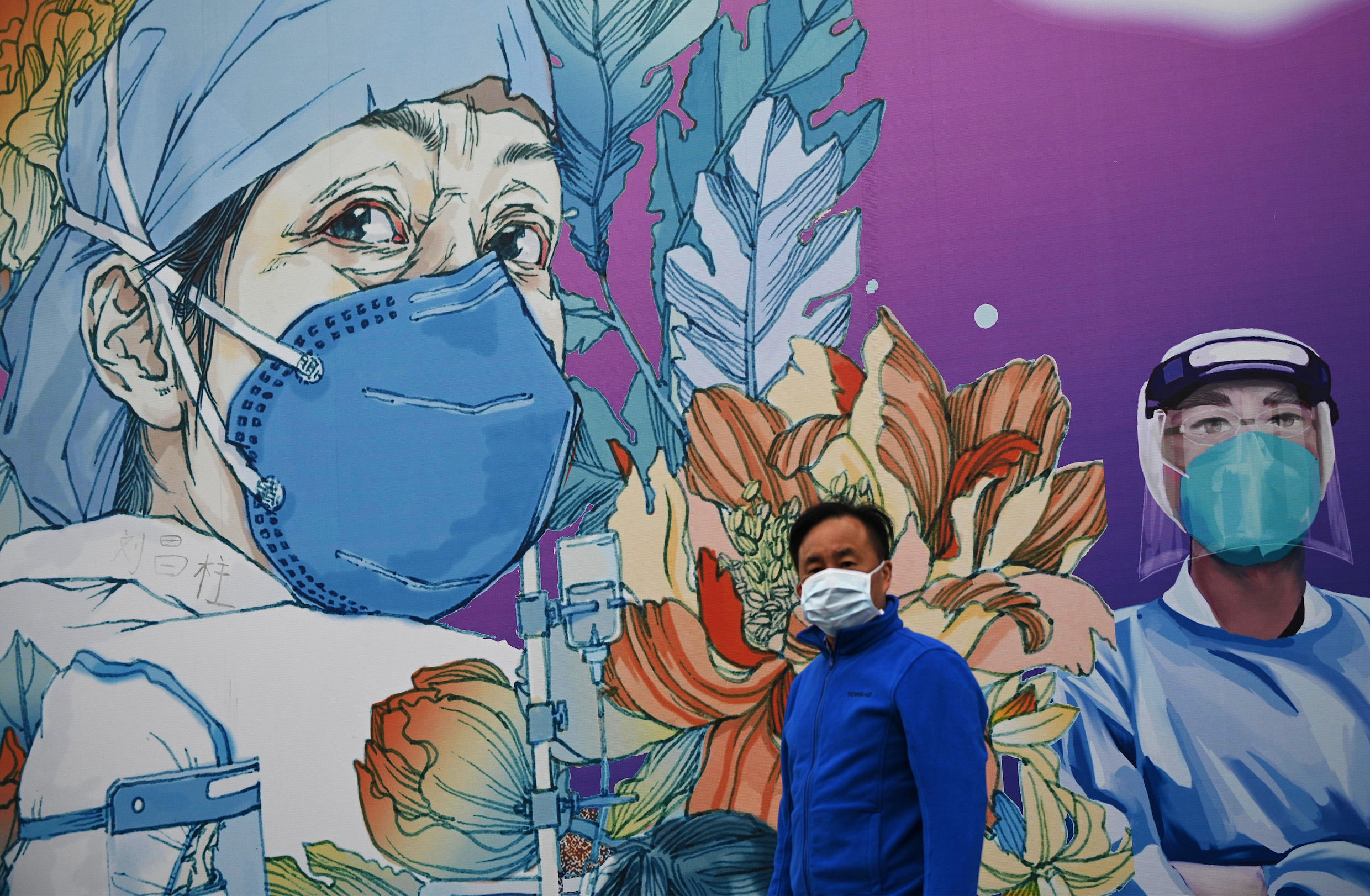 A man wearing a facemask walks in front of a mural at Leishenshan Hospital in Wuhan, China