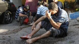 Deux blessés attendent de recevoir de l'aide, après qu'une roquette ait frappé leur maison, le 26 mai 2013 dans la banlieue sud de Beyrouth.