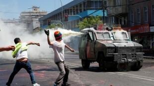 智利全国性抗议风暴愈演愈烈导致政府取消亚太经合峰会。图为瓦尔帕莱索市警方与民众对峙的场景。