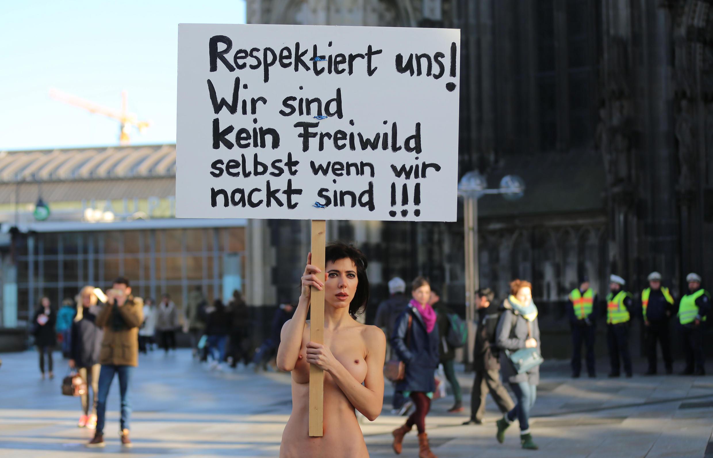 """Artista Milo Moire com um cartaz escrito: """"Respeite-nos!"""" em frente à Catedral de Colônia."""