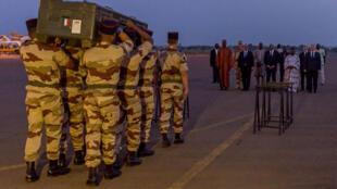 Dans le silence, des militaires français portent les cercueils-containers  sur le tarmac. D'abord celui de Claude, puis celui de Ghislaine, posés quelques minutes sur des tréteaux au pied de l'avion. Un moment de recueillement pour tout le monde.